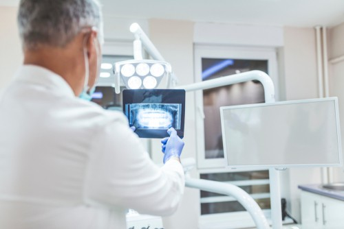 dentist examines x-ray - Avery & Meadows Dental Partnership